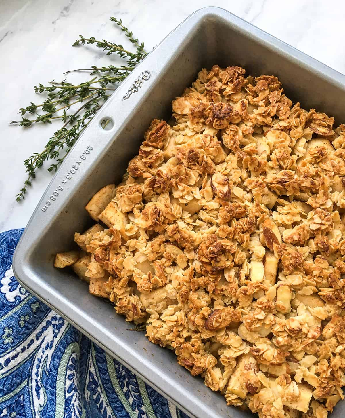 baked apple crisp in square metal pan with blue napkin and sprig of thyme on the side