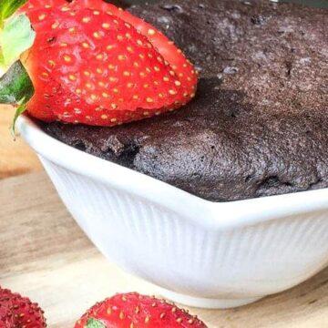 white mug with keto chocolate cake baked inside and strawberry slice garnish