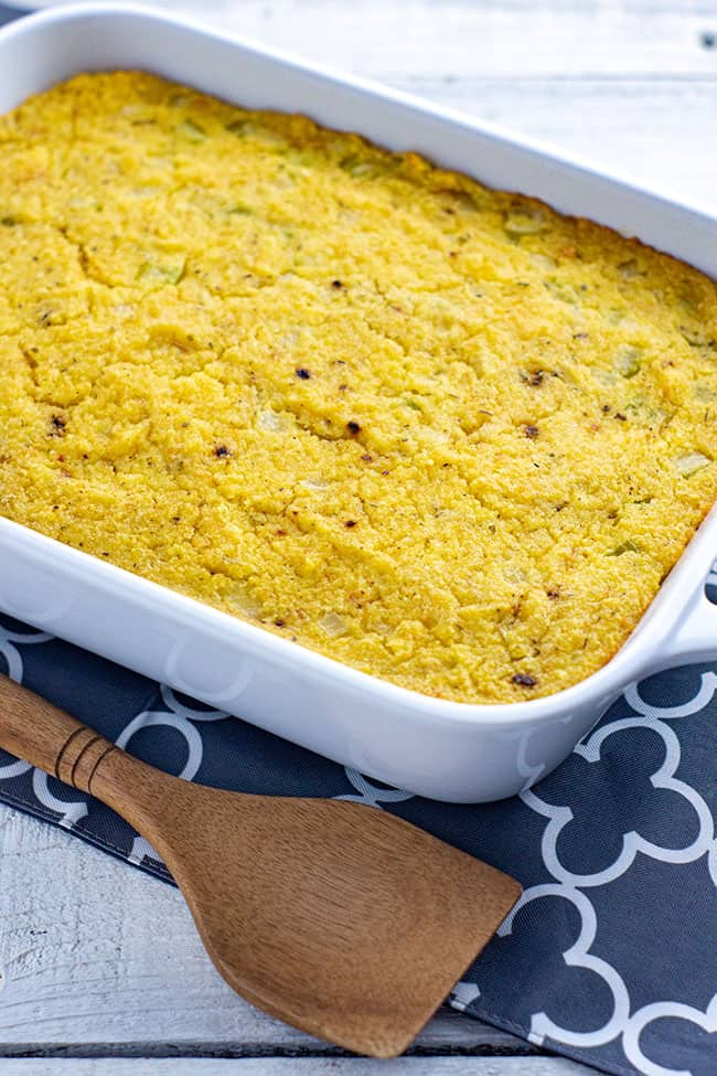 baked cornbread dressing in a white casserole dish with a wooden serving spoon