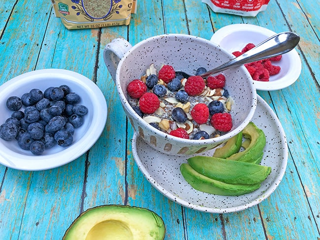 keto low carb oatmeal in a white bowl topped with blueberries, raspberries, and almond slices. Sliced avocado on the side.