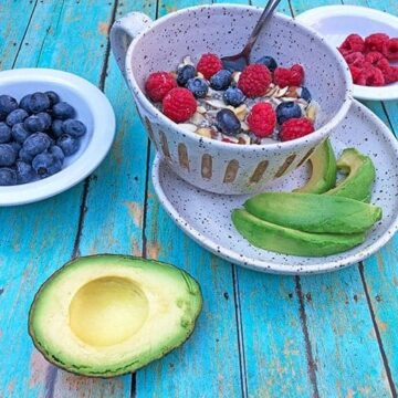 low carb oatmeal in white bowl with blueberries and raspberries on top and avocado slices on side