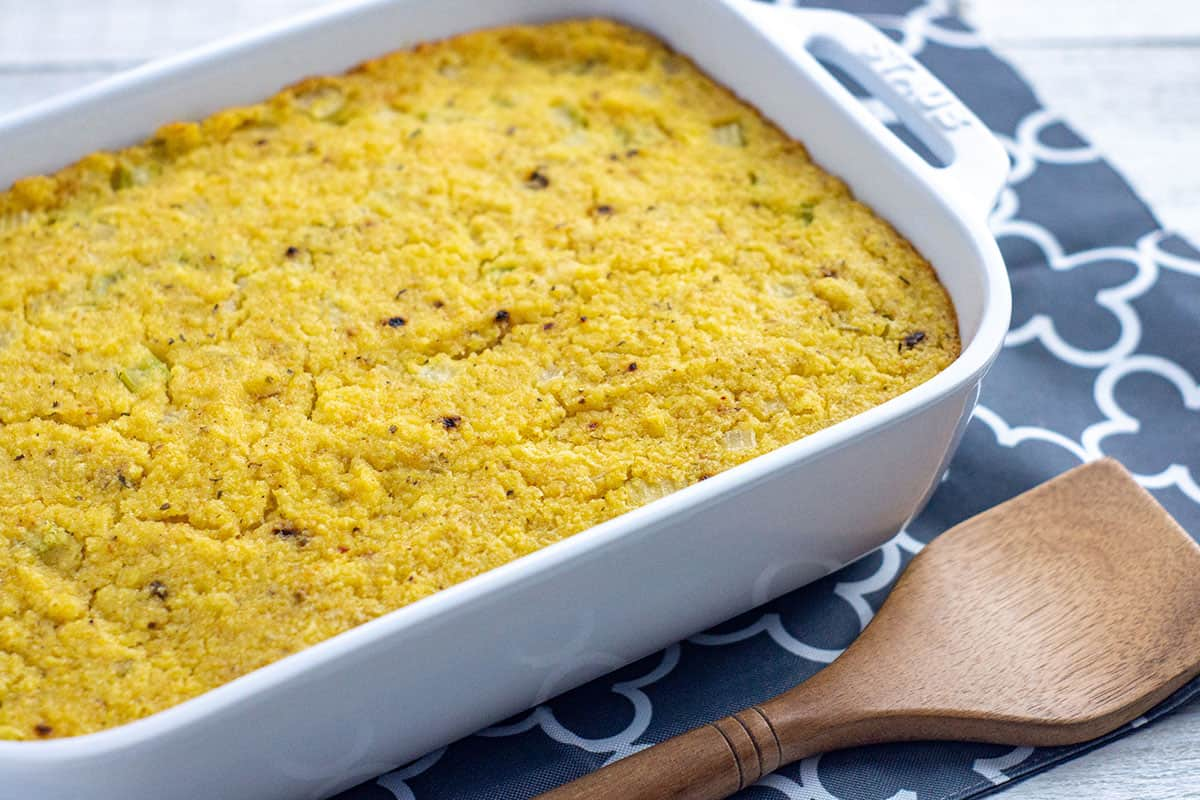 baked cornbread dressing in white rectangular casserole dish with wooden serving spatula on the side