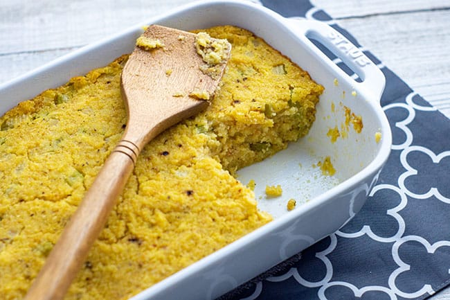southern cornbread dressing in a white casserole dish with a wooden spoon