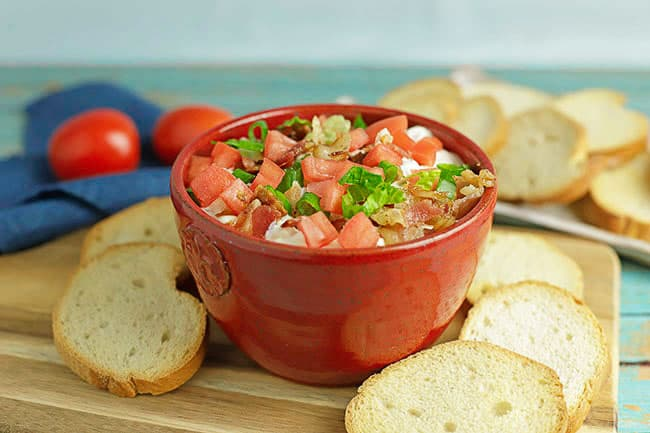 BLT Dip in red bowl with crostini slices on side