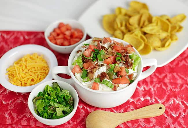 BLT Dip in white bowl with Corn Chips, cheddar, tomatoes and lettuce on the side