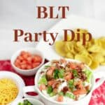 BLT Party Dip in white bowl with chips, tomatoes, and cheese on red napkin
