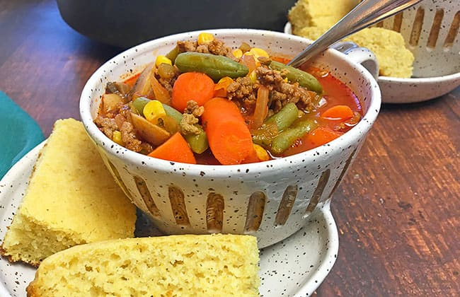easy hamburger vegetable soup in bowl with cornbread