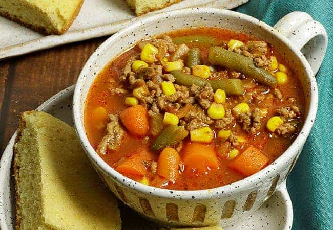 hamburger vegetable soup in white bowl with cornbread slices next to blue teal napkin