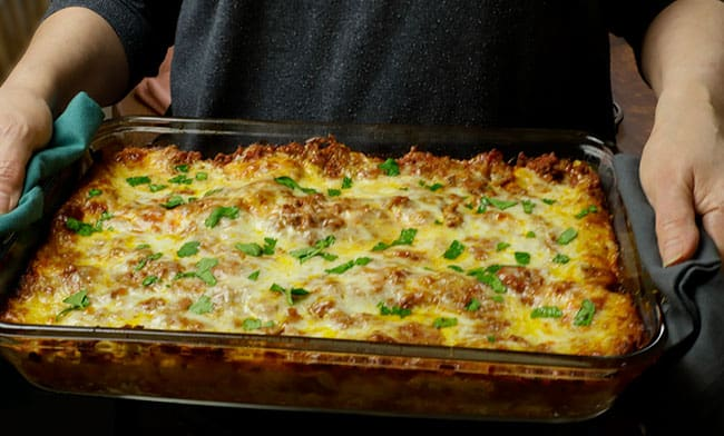 hands holding dish of Italian lasagna with meat and sausage