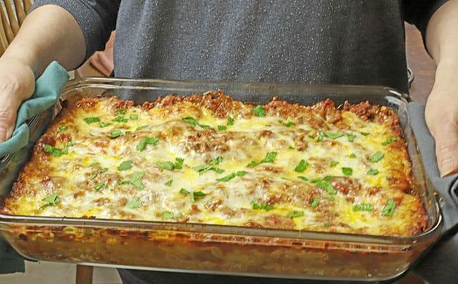 easy meat lasagna serving hands