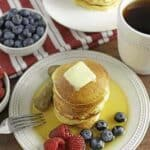 low carb pancakes on white plate with berries on side and syrup on top