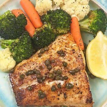 cooked fish on plate with mixed vegetables on side
