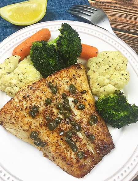 cooked red snapper fillet with lemon butter caper sauce on a white plate with cauliflower, carrots and broccoli