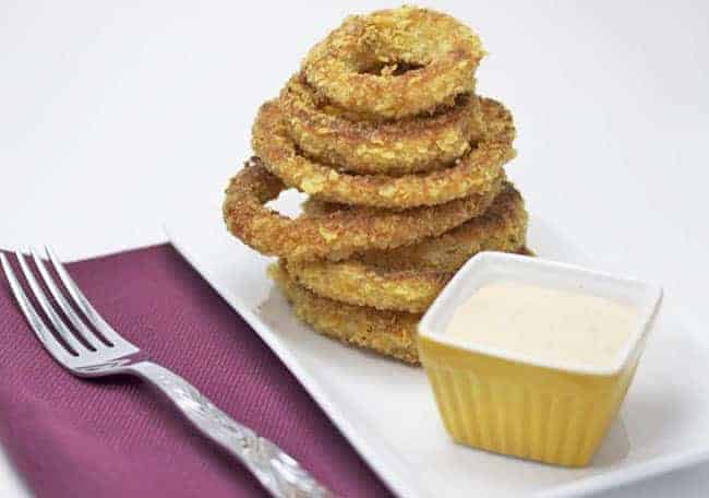 baked onion rings in white plate with dipping sauce on the side