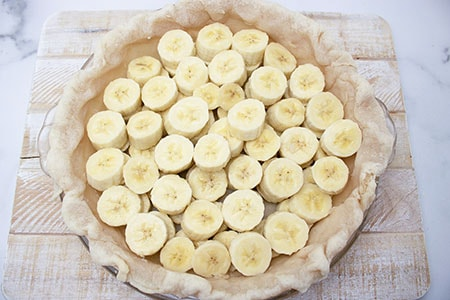 banana slices in bottom of pie crust