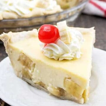 pie topped with whipped cream, banana slice, and cherry