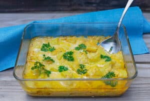 cooked casserole in glass dish with silver serving spoon