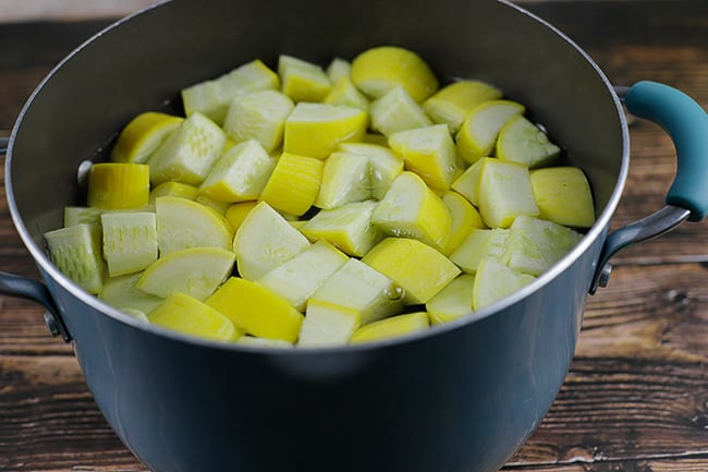 quartered squash in pot of water