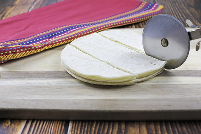 layer of tortillas being sliced with a pizza cutter