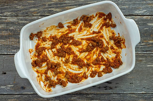 thin layer of red meat sauce in white casserole dish