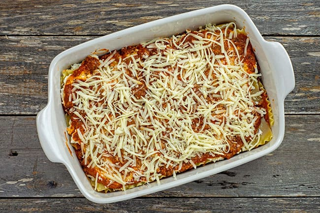 3 layer assembled meat lasagna in a white casserole dish with cheese on top prior to baking