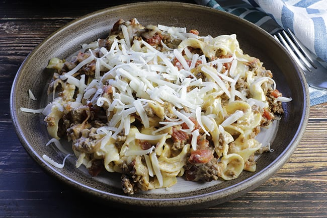 baked ground beef noodle casserole on tan plate