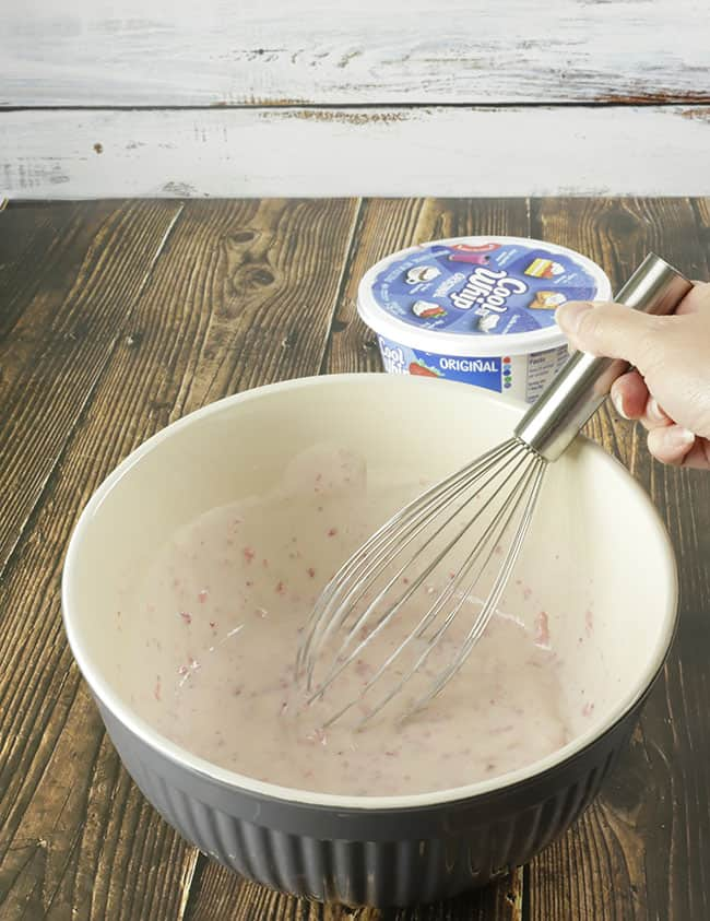 hand holding whisk that is mixing together strawberry purée, sweetened condensed milk, lime and tequila for no bake strawberry cream pie filling