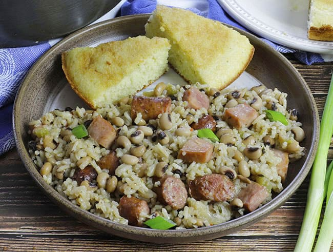 plate of hoppin john with two slices of cornbread