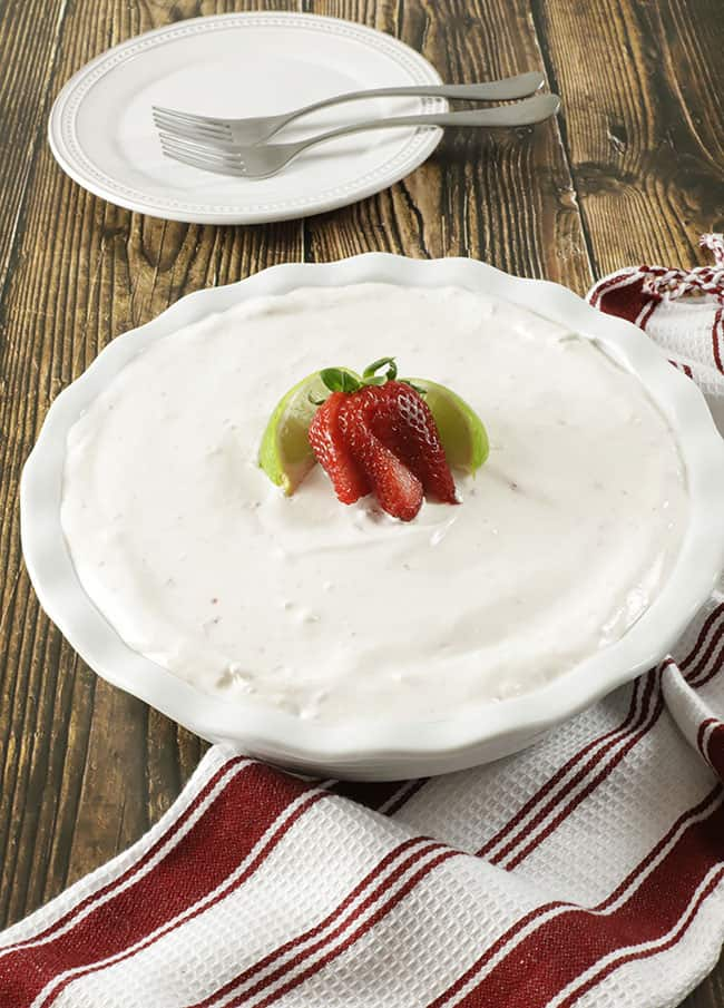 completed no bake strawberry cream pie in a white fluted pie dish with a red and white striped dish towel, garnished with lime wedges and strawberry slices