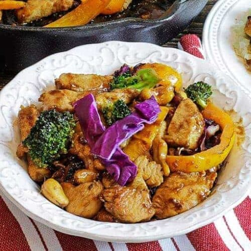 cashew chicken and cabbage stir fry on white plate