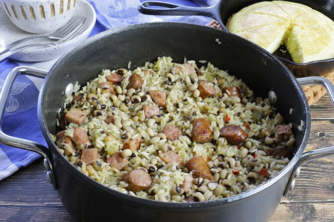 cooked hoppin john in large black pot with cornbread in the background