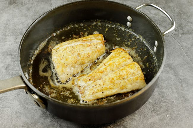 snapper fillets in a sauté pan with butter