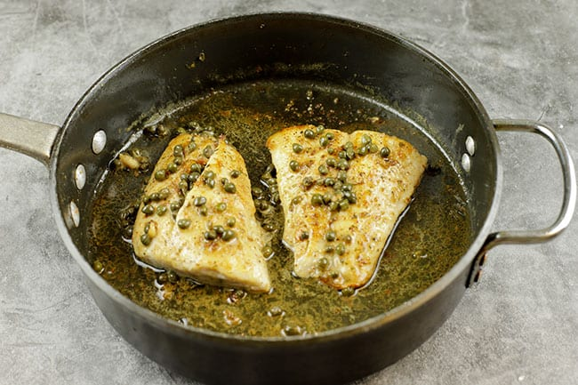 capers on red snapper fillets in a sauté pan with melted butter