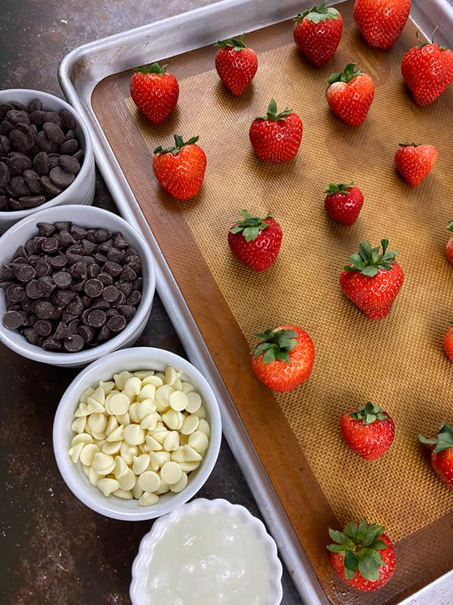 Chocolate Covered Strawberries ingredients laid out on table with strawberries on sheet pan