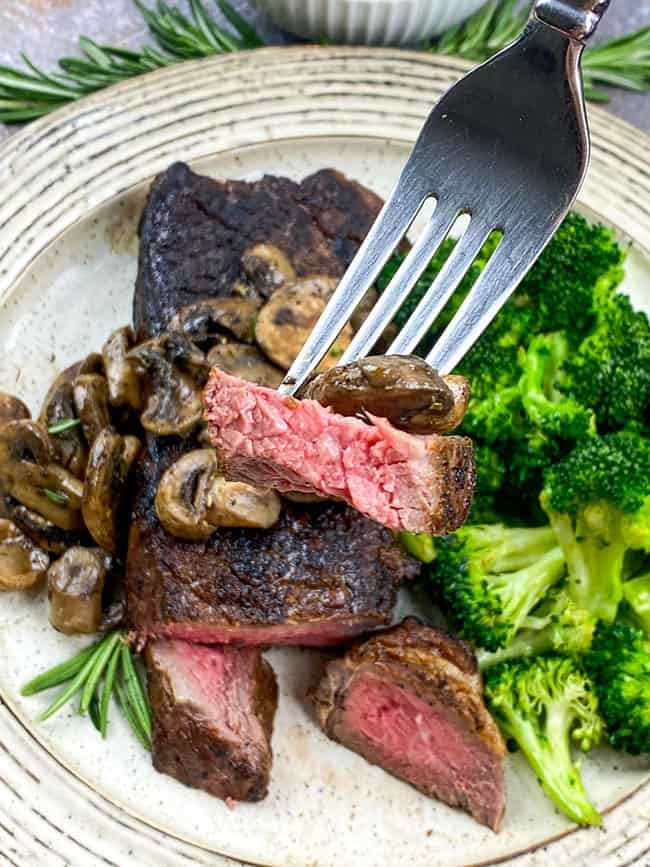 Medium rare strip steak with mushrooms and broccoli
