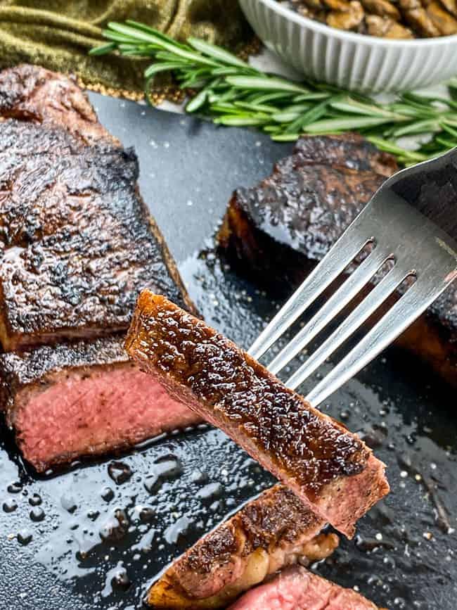 cooked medium rare strip steak with slice on fork
