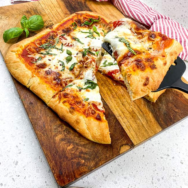 baked pizza on wooden cutting board with slice on spatula and red striped napkin in background