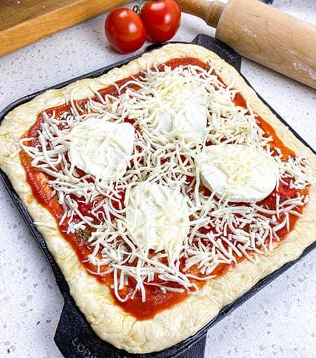 add mozzarella slices and shredded mozzarella to pizza