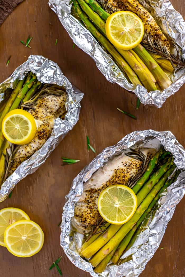 Lemon Pepper Chicken with rosemary and asparagus inside foil packet with lemon slices on top