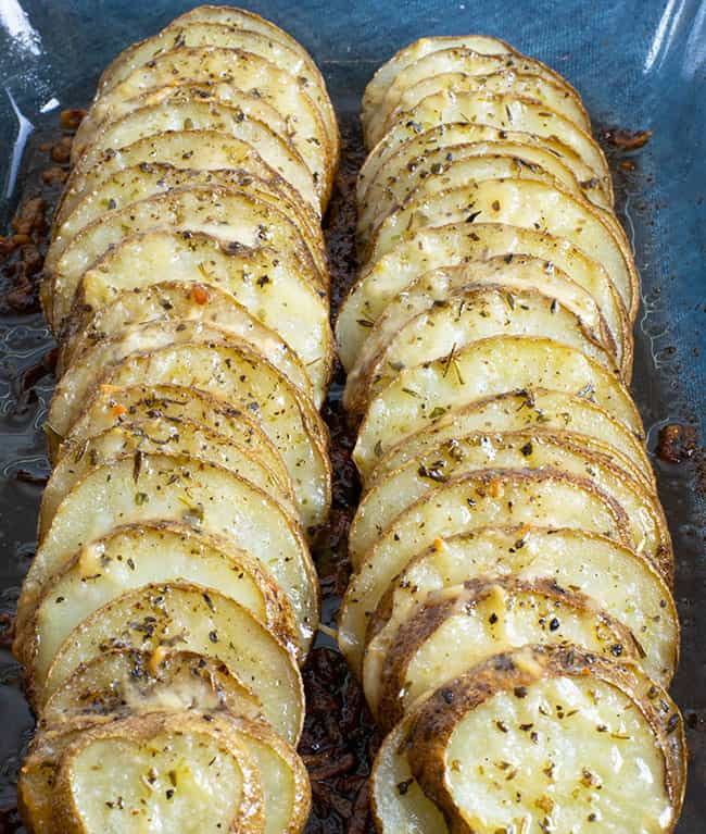 baked sliced potatoes topped with butter herbs and parmesan cheese in oblong glass casserole dish