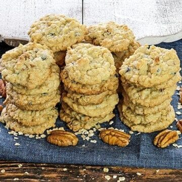 stacked baked cookies on blue napkin with pecan halves next to them