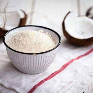 bowl of coconut flour with two coconut halves and hammer in background