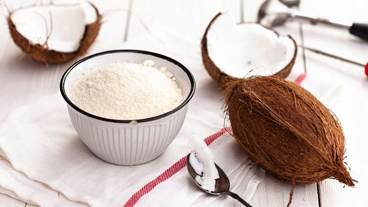 coconut flour in bowl with whole coconut next to it