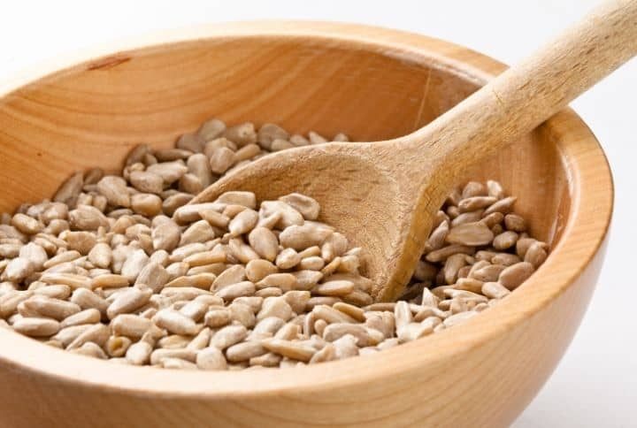 shelled sunflower seeds in wooden bowl with wooden spoon