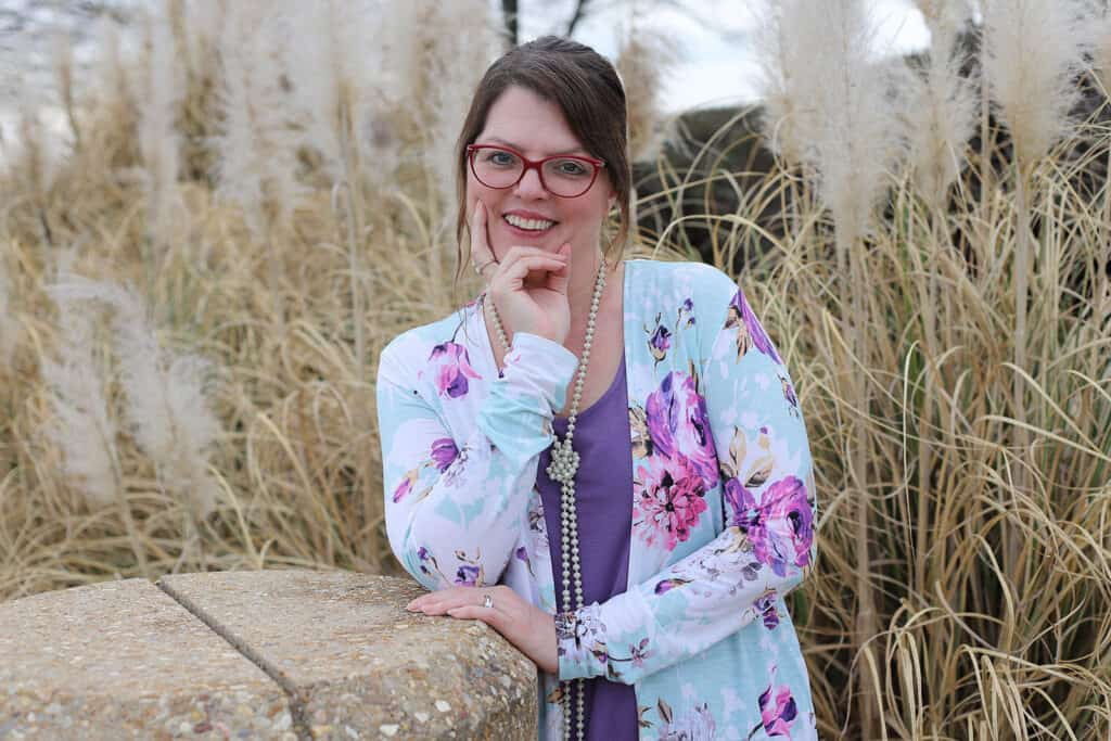 Profile picture pose outside in front of tall brown grass in lavender floral blouse