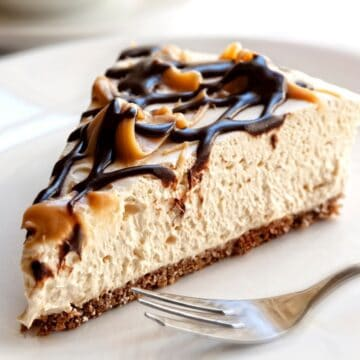 cheesecake slice topped with peanut butter and chocolate syrup on white plate with fork