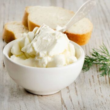 cream cheese in white bowl with clear spoon and 3 slices of french bread in background