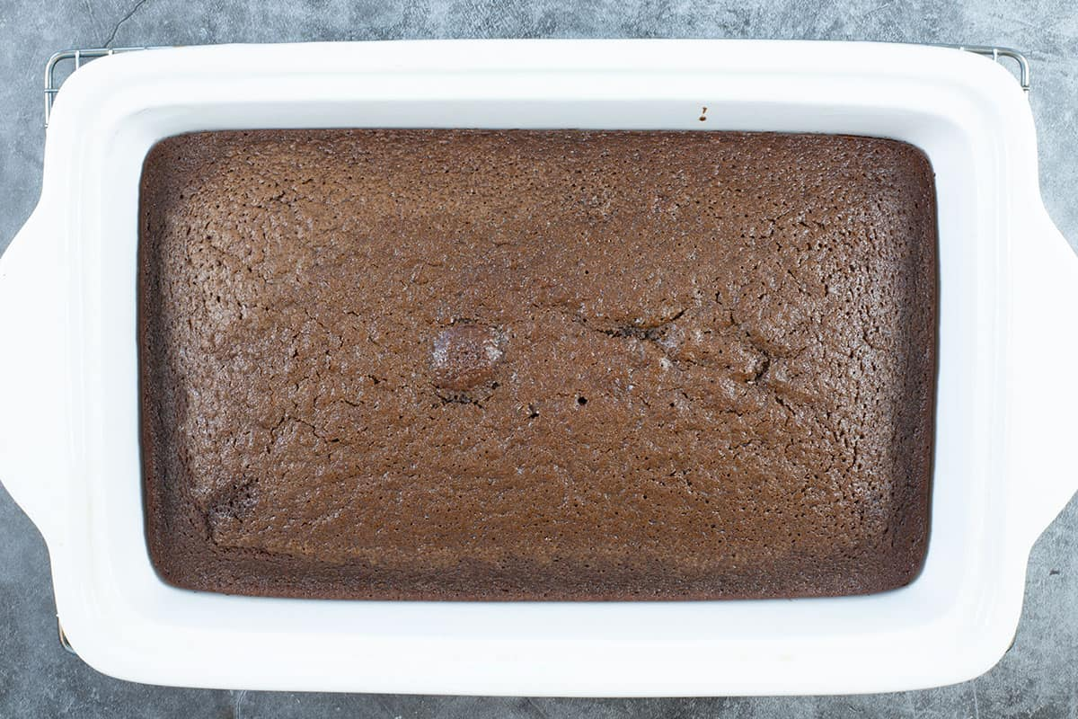 baked cake unfrosted in a rectangular white cake pan