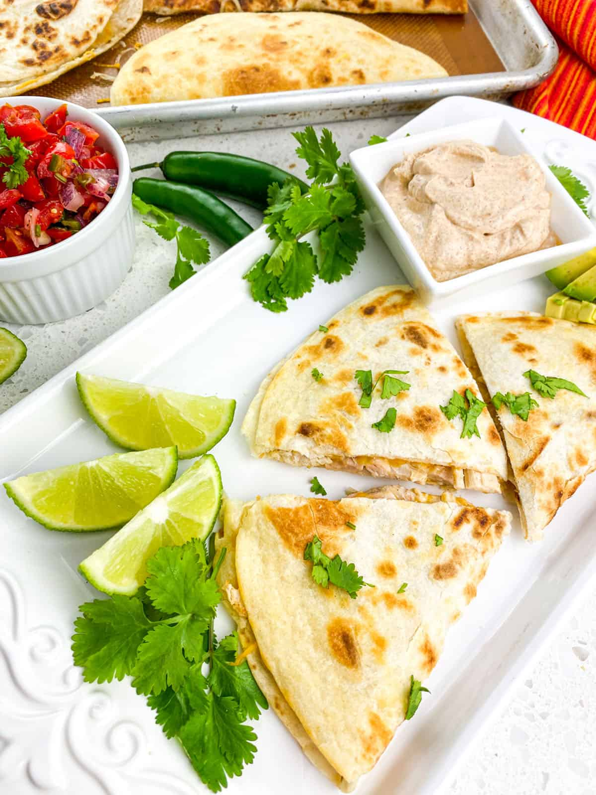 cooked quesadillas cut into thirds on white rectangular plate with lime wedges and seasoned sour cream and pico de gallo on side