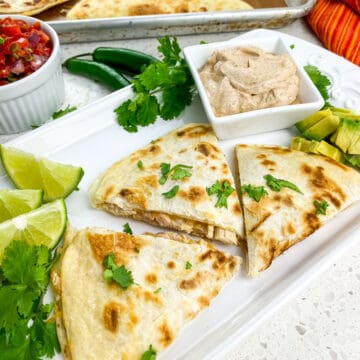 cooked quesadillas cut into thirds on white rectangular plate with lime wedges and seasoned sour cream